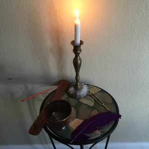 An altar with tools for the five senses: a candle for Sight, incense for Smell, some white wine for Taste, a feather for Touch, a tuning fork for Sound.
